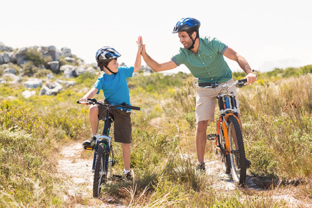 dad and son: Father and son biking through mountains on a sunny day Stock Photo