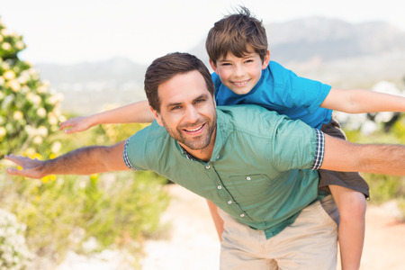 father and son: Father and son hiking through mountains on a sunny day Stock Photo