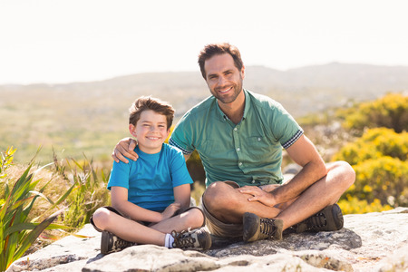adventuring: Father and son hiking through mountains on a sunny day Stock Photo