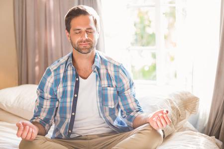 Knappe man doet yoga op zijn bed thuis in de slaapkamer