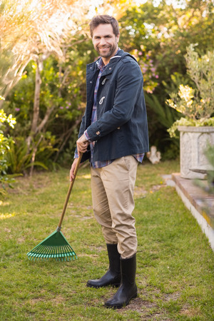 raking: Handsome man raking in his garden on a sunny day Stock Photo
