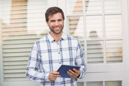 uomo felice: Felice l'uomo che sorride alla macchina fotografica tablet azienda in una giornata di sole