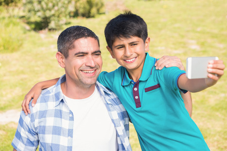 father and child: Father and son in the countryside taking selfie on a sunny day