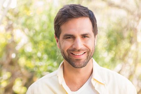 Šťastný muž s úsměvem na kameru slunečného dne