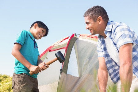 pitching: Father and son pitching their tent on a sunny day
