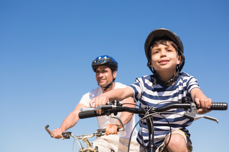 sunny day: Father and son on a bike ride on a sunny day Stock Photo