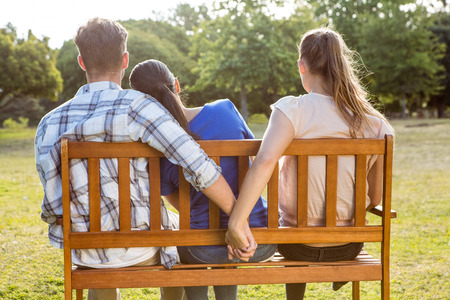 unfaithful: Man being unfaithful in the park on a sunny day Stock Photo