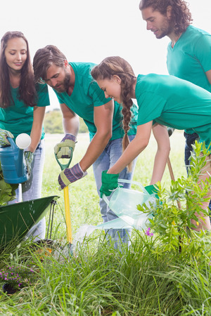a rural community: Happy friends gardening for the community on a sunny day