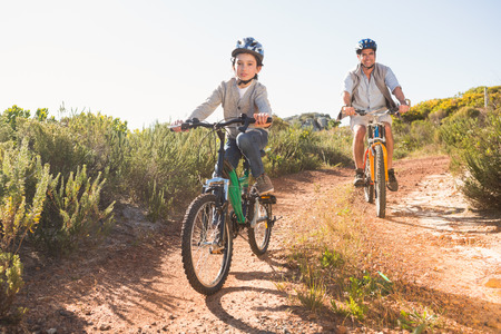Father and son on a bike ride on a sunny day Stock Photo