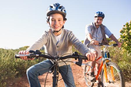 화창한 날에 아버지와 아들이 자전거를 타다.