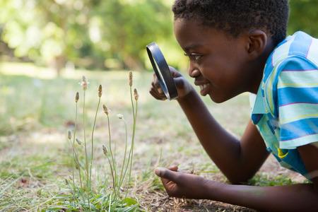 niños negros: Niño lindo mirando a través de la lupa en un día soleado