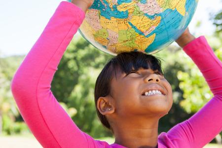 planeta tierra feliz: Ni�a linda que sostiene el mundo en un d�a soleado