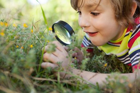 Gelukkig weinig jongen die door een vergrootglas op een zonnige dag