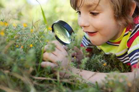 discover: Happy little boy looking through magnifying glass on a sunny day