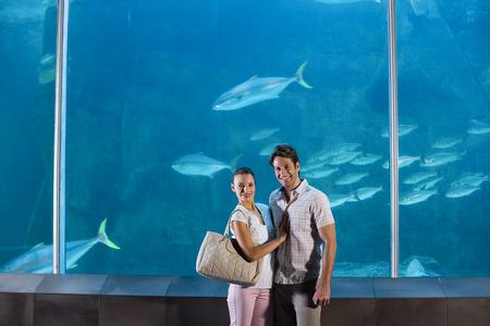 fish tank: Pareja feliz al lado de la pecera en el acuario Foto de archivo
