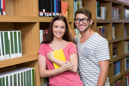 schoolmate: Students in the library smiling at camera at the university Stock Photo