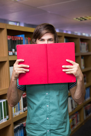 covering the face: Student covering face with book in library at the university