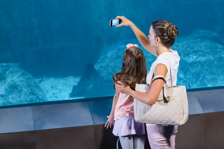 fishtank: Happy mother and daughter taking photo of fish at the aquarium