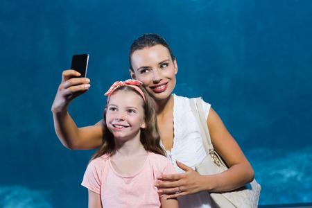 fishtank: Happy mother and daughter taking selfie at the aquarium