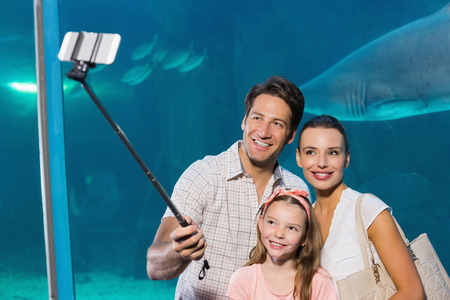 fishtank: Happy family using selfie stick at the aquarium