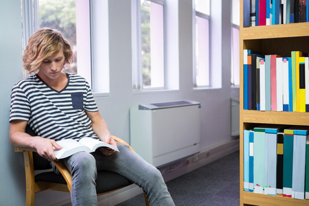 revising: Student reading in library at the university