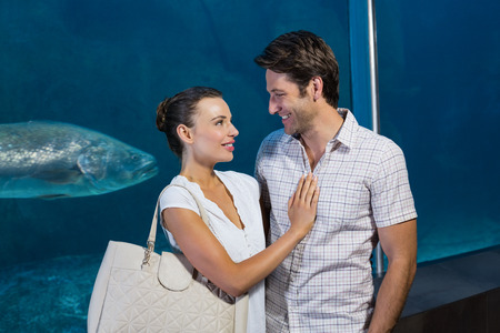 fish tank: Happy couple beside the fish tank at the aquarium
