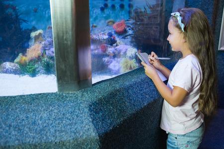 fish tank: Cute girl looking at fish tank at the aquarium Stock Photo