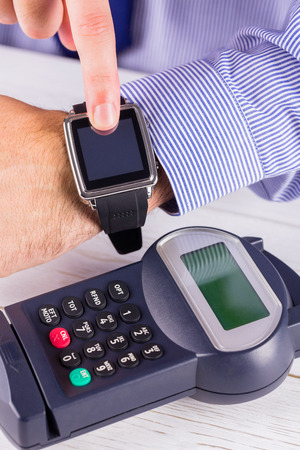 Man using smart watch to express pay  on a wooden table Stock Photo