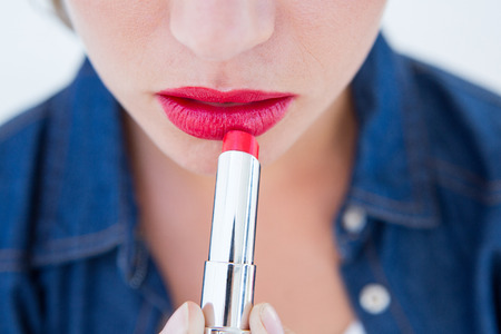Woman putting red lipstick on white background Stockfoto