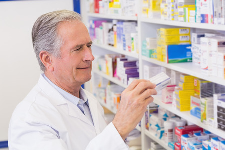 Senior pharmacist taking medicine from shelf at the hospital pharmacy Stok Fotoğraf