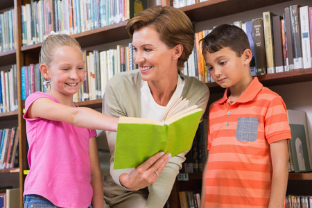 standing together: Teacher reading book with pupils at library at elementary school