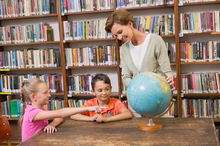 early 40s: Pupils and teacher looking at globe in library
