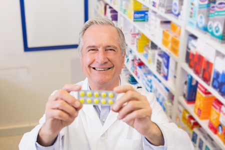 holding up: Senior pharmacist holding up blister packs at hospital pharmacy