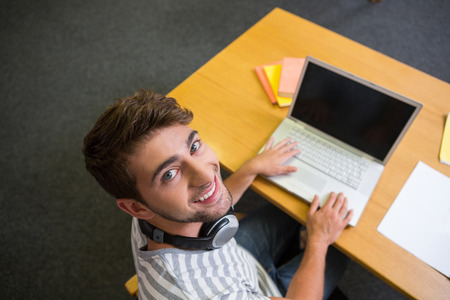 headset computer: Student studying in the library with laptop at the university