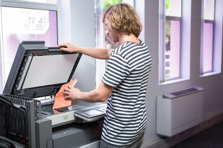 Student photocopying his book in the library at the university photo