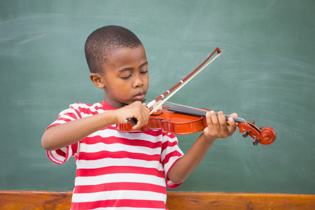 early childhood: Cute pupil playing violin in classroom at the elementary school