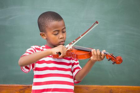 violines: Lindo alumno que toca el violín en el aula en la escuela primaria
