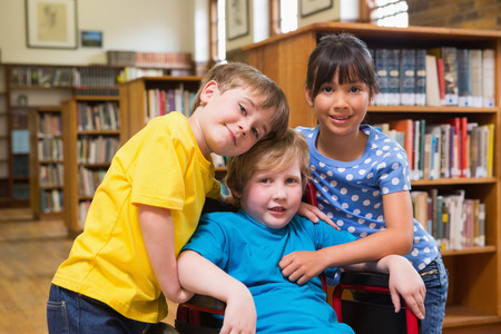 discapacidad: Alumnos lindos que abrazan en la biblioteca en la escuela primaria