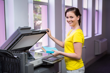 xerox: Student photocopying her book in the library at the university