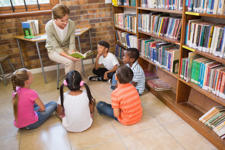 early childhood: Cute pupils and teacher having class in library at the elementary school