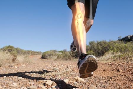Digital composite of Highlighted leg bones of jogging man