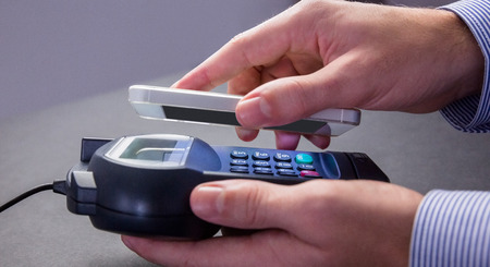 eftpos: Man using smartphone to express pay against grey background