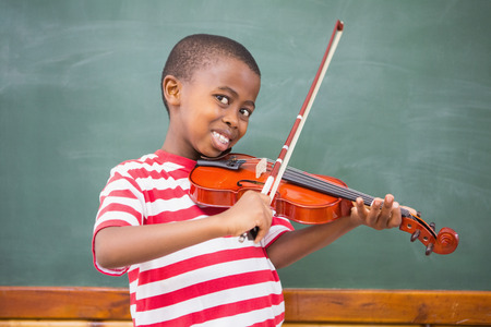 musical instrument: Happy pupil playing violin in classroom at the elementary school