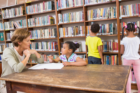 early 40s: Teacher helping pupil in library at elementary school