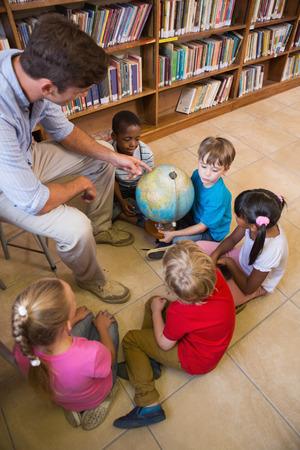 escuela primaria: Alumnos lindos y profesor que miran el globo en la biblioteca de la Escuela Primaria Foto de archivo