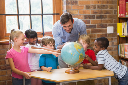 early 30s: Cute pupils and teacher looking at globe in library at elementary school Stock Photo