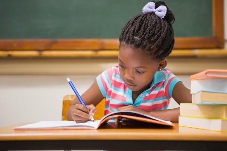 persona escribiendo: Alumnos lindos que escriben en el escritorio en el aula en la escuela primaria