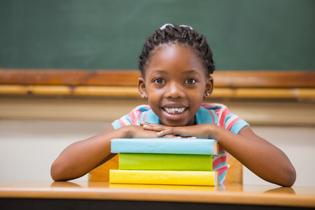 girls back to back: Smiling pupil sitting at her desk at the elementary school