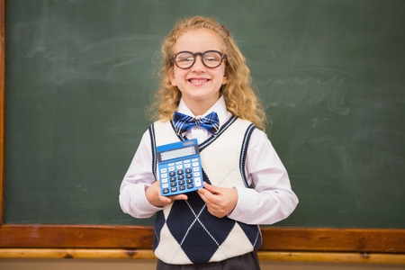pupil: Smiling pupil holding calculator at elementary school