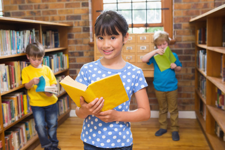 kids reading book: Cute pupil smiling at camera in library at elementary school Stock Photo